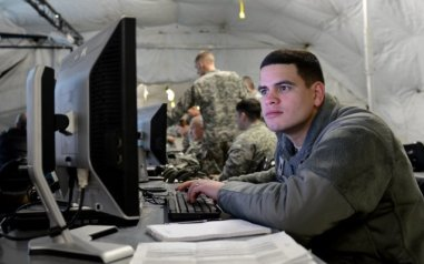 Soldier looking at a computer screen.